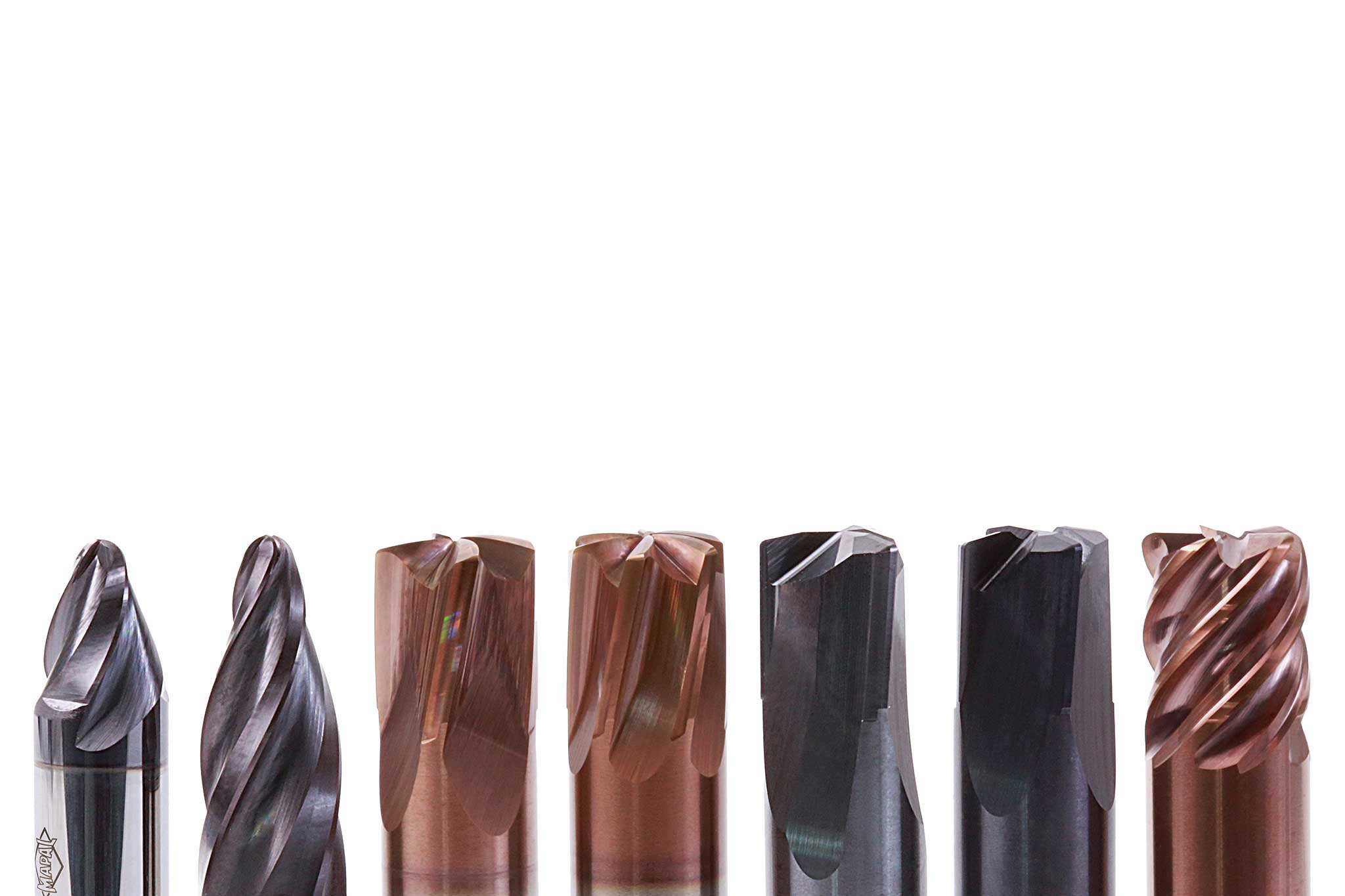 There are seven solid carbide milling cutters placed in a row. They have different shapes and coatings.