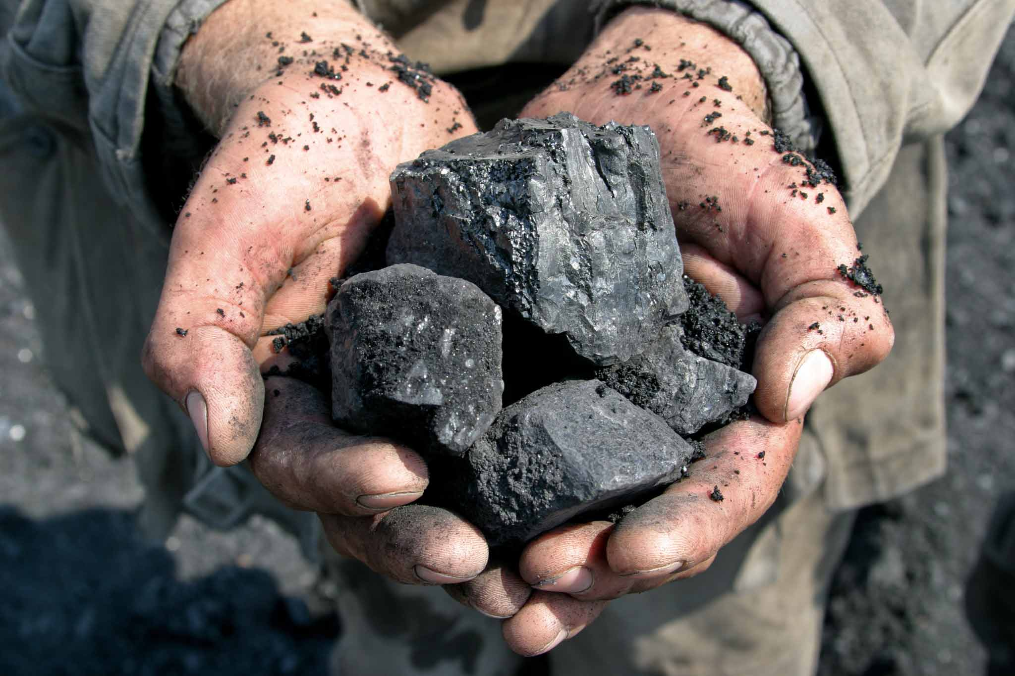 The picture shows two hands holding rocks from mining.