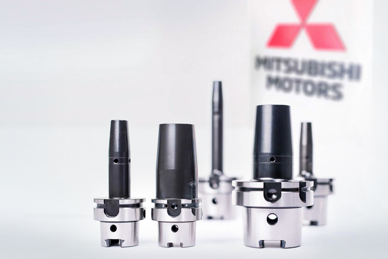Five shrink chucks from MAPAL are placed in front of the Mitsubishi Motors logo.